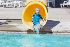Muchacho joven que monta abajo de un tobogán acuático amarillo Fotografía de archivo