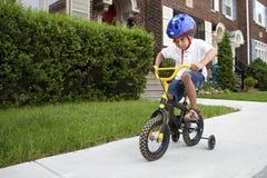 Muchacho joven que monta su bicicleta Foto de archivo libre de regalías