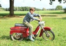 Muchacho joven que monta una moto Imagen de archivo