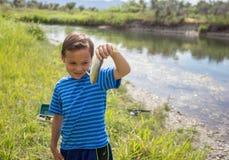 Muchacho joven que muestra los pescados que él cogió Imagen de archivo