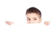 Muchacho joven que oculta detrás de una cartelera y que hace una cara en cámara Imagen de archivo