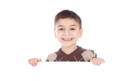 Muchacho joven que oculta detrás de una cartelera y que hace una cara en cámara Fotografía de archivo