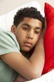 Muchacho joven que parece triste en el sofá Imágenes de archivo libres de regalías