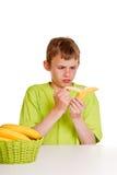 Muchacho joven que pela un plátano con hastío Imagenes de archivo