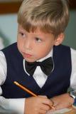 Muchacho joven que piensa en sala de clase Fotos de archivo libres de regalías