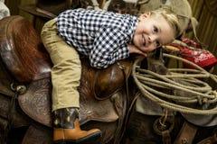 Muchacho joven que pone en una sonrisa occidental de la silla de montar del vaquero Foto de archivo libre de regalías