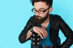 Muchacho joven que presenta con la guitarra contra la pared azul Foto de archivo