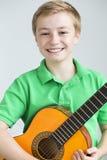 Muchacho joven que presenta con una guitarra Foto de archivo