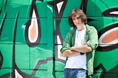 Muchacho joven que presenta contra una pared de la pintada Imagenes de archivo