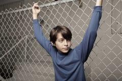Muchacho joven que presenta en una cerca de la encadenamiento-conexión Fotografía de archivo
