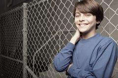 Muchacho joven que presenta en una cerca de la encadenamiento-conexión Foto de archivo