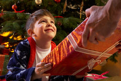 Muchacho joven que recibe el regalo de Navidad Fotografía de archivo
