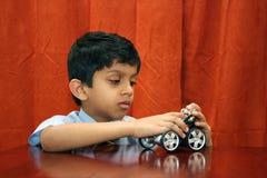 Muchacho joven que repara el coche del juguete Foto de archivo libre de regalías