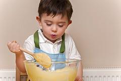 Muchacho joven que revuelve la masa en un bol de vidrio Foto de archivo libre de regalías