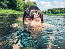 Muchacho joven que salpica en el agua en el verano Fotos de archivo