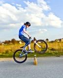 Muchacho joven que salta con su bici de la daga escocesa sobre una barrera en el stree Imagenes de archivo