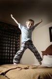 Muchacho joven que salta en la cama Imagen de archivo libre de regalías