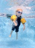 Muchacho joven que salta en una piscina Fotografía de archivo