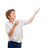 Muchacho joven que señala con las manos en el espacio de la copia. Foto de archivo