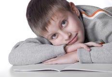Muchacho joven que se acuesta en un suelo con el copy-book Imagen de archivo libre de regalías