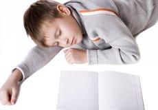 Muchacho joven que se acuesta en un suelo con el copy-book Imagen de archivo