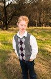 Muchacho joven que se coloca en campo verde Fotos de archivo libres de regalías