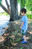 Muchacho joven que se coloca en la orilla de un lago Imagen de archivo