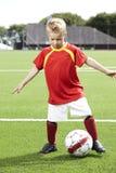Muchacho joven que se coloca en un campo de fútbol Foto de archivo libre de regalías