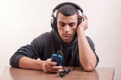 Muchacho joven que se divierte como él escucha su reproductor Mp3 con grande Imagen de archivo