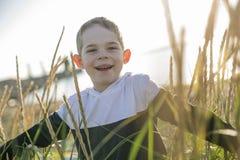 Muchacho joven que se divierte en la playa en la puesta del sol Fotografía de archivo libre de regalías
