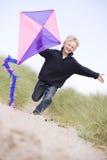 Muchacho joven que se ejecuta en la playa con la sonrisa de la cometa Imágenes de archivo libres de regalías
