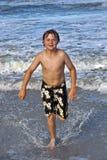 Muchacho joven que se ejecuta a través del agua en la playa Foto de archivo libre de regalías