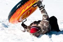 Muchacho joven que se estrella en el tubo en la nieve Imagen de archivo libre de regalías