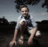 Muchacho joven que se pone en cuclillas y que sonríe Fotos de archivo libres de regalías