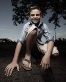 Muchacho joven que se pone en cuclillas y que sonríe Foto de archivo