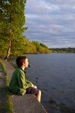 Muchacho joven que se reclina en la cara del lago Imágenes de archivo libres de regalías