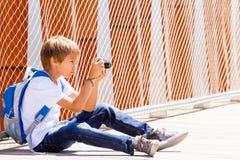 Muchacho joven que se sienta con una cámara digital y que toma imágenes en la calle Fotos de archivo