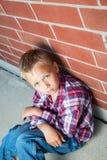 Muchacho joven que se sienta contra una pared Fotos de archivo libres de regalías