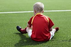 Muchacho joven que se sienta en campo de fútbol Fotos de archivo