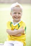 Muchacho joven que se sienta en campo de fútbol Foto de archivo libre de regalías