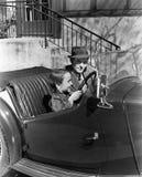 Muchacho joven que se sienta en el asiento de conductor del coche con su padre (todas las personas representadas no son vivas más foto de archivo libre de regalías