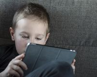 Muchacho joven que se sienta en el sofá en sala de estar e historietas de observación en la tableta Retrato de un niño elegante d foto de archivo