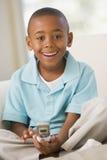 Muchacho joven que se sienta en un sofá, envío de mensajes de texto fotos de archivo libres de regalías