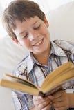 Muchacho joven que se sienta en un sofá que lee un libro Imágenes de archivo libres de regalías
