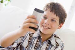 Muchacho joven que se sienta en un sofá Texting Fotos de archivo libres de regalías