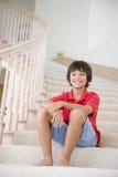 Muchacho joven que se sienta en una escalera en el país Fotografía de archivo libre de regalías