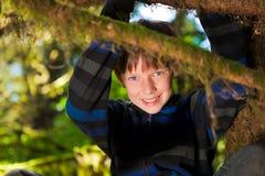 Muchacho joven que se sienta en una sonrisa del árbol Imagen de archivo
