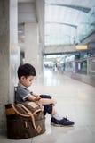 Muchacho joven que se sienta solamente en un vestíbulo Imagen de archivo