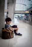 Muchacho joven que se sienta solamente en un vestíbulo Fotos de archivo libres de regalías