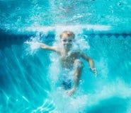 Muchacho joven que se zambulle bajo el agua en piscina Imagen de archivo